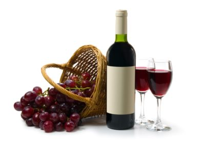 Two glasses with red wine on a white background. A dark wine bottle with a empty label. Red ripe grape in wooden basket.